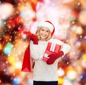 shopping, sale, gifts, christmas, x-mas concept - smiling woman in santa helper hat with shopping bags and gift boxes