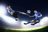 Two soccer players in mid air kicking the soccer ball