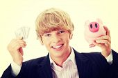 Young business holding piggy bank and dollars