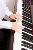 music and instrument concept - close up of child hands playing the piano