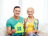 moving, home and couple concept - smiling couple with green house and keys in new home
