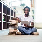 Full length portrait of young male student with stacked books and digital tablet sitting on floor at