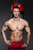 Bodybuilding. Attractive man with boxing bag