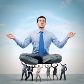 Young businessman sitting in lotus pose and supported by colleagues