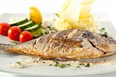Grilled Dorado with Mashed Potato. Garnished with Lemon and Vegetables