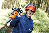 stock photo of chainsaw  - Portrait of lumberjack logger worker in protective workwear with chainsaw at forest - JPG