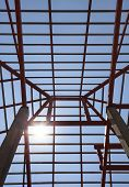Metal Structure Of House Roof In Home Construction Site And Sun Shining On Blue Sky Use For Construc
