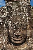 ANGKOR THOM, CAMBODIA - DECEMBER 20, 2013: Ancient stone face of Bayon temple, Angkor, Cambodia