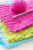 Homemade crochet dishcloths made of vibrant colored yarn. Crochet hook and a ball of yarn is along s