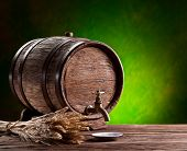 Old oak barrel on a wooden table. Behind blurred green background.