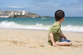 image of st ives  - Child sitting on a beach looking at the sea in a Cornish seaside village and port of St - JPG