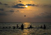 Silhouetted Group Of Boy Are Playing A Ball In The Sea