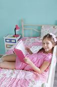 Portrait of 7 years old school girl reading a book on pink bed in her nursery at home