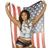 Beautiful young woman wearing denim shorts and jacket holding American flag isolated against white b