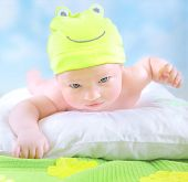 Closeup portrait of cute little baby wearing funny frog costume and lying down on imagine floral fie