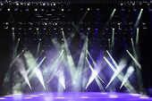 picture of illuminating  - Illuminated empty concert stage with smoke and rays of light - JPG