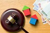 wooden houses with money and judge gavel on wooden table