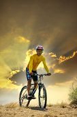 young man riding moutain bike mtb on land dune against dusky sky in evening background  use for spor