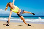 Young attractive woman doing kettle bell exercises outside. Fitness woman working out at the beach.