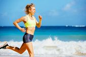 Athletic Fitness Woman Running on the Beach. Female Runner Jogging. Outdoor Workout. Fitness Concept