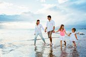 Happy young family walking on the beach at sunset. Happy Family Lifestyle