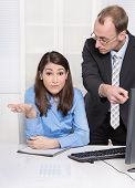 Young businesswoman with her manager at desk - unhappy, problem