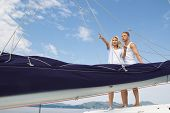 Attractive couple standing on a sailing boat - love.
