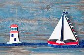 Summer wooden background in blue with sailboat and lighthouse decoration