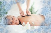 Close up of a blonde woman experiencing a stone therapy against snowflake frame