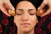 Facial massage with special marble eggs of a young woman.