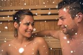 Cheerful couple relaxing in a sauna and chatting against snow falling