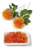 Dish with imitation Saffron from safflower on white background