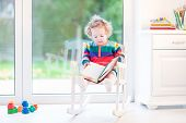 Cute Funny Toddler Girl Reading In A White Rocking Chair At A Big Window