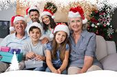 Extended family in Christmas hats with gift boxes in living room against fir tree forest and snowflakes
