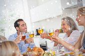 Family raising their glasses at thanksgiving dinner against snow falling