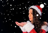 Pretty brunette in santa outfit blowing over her hands against snow