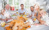 Composite image of Focus on the roast turkey in front of family against snowflakes