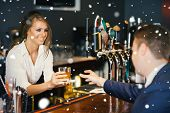 Beautiful waitress serving handsome businessman against snow falling