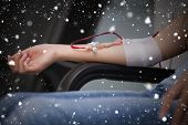 Composite image of woman getting a transfusion against snow falling