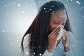 Composite image of close up of woman blowing her nose against snow