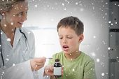 Doctor giving little boy cough syrup against snow falling