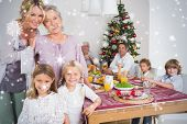 Composite image of Three generations of women at christmas time against snow falling