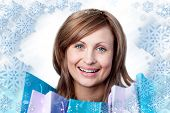 Composite image of radiant woman with shopping bags against snow
