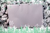 Composite image of snow frame against lined paper notebook on crumpled paper