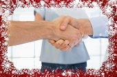 Composite image of casual businessmen shaking hands against snow