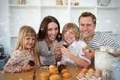 Cute children eating muffins with their parents against snow