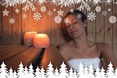 Happy brunette woman sitting in a sauna against fir tree forest and snowflakes