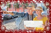 Happy tourist couple using map in the city against snow