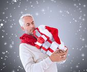Composite image of happy festive man with gifts against grey vignette