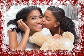 Pretty woman lying on bed with her daughter kissing cheek against snow